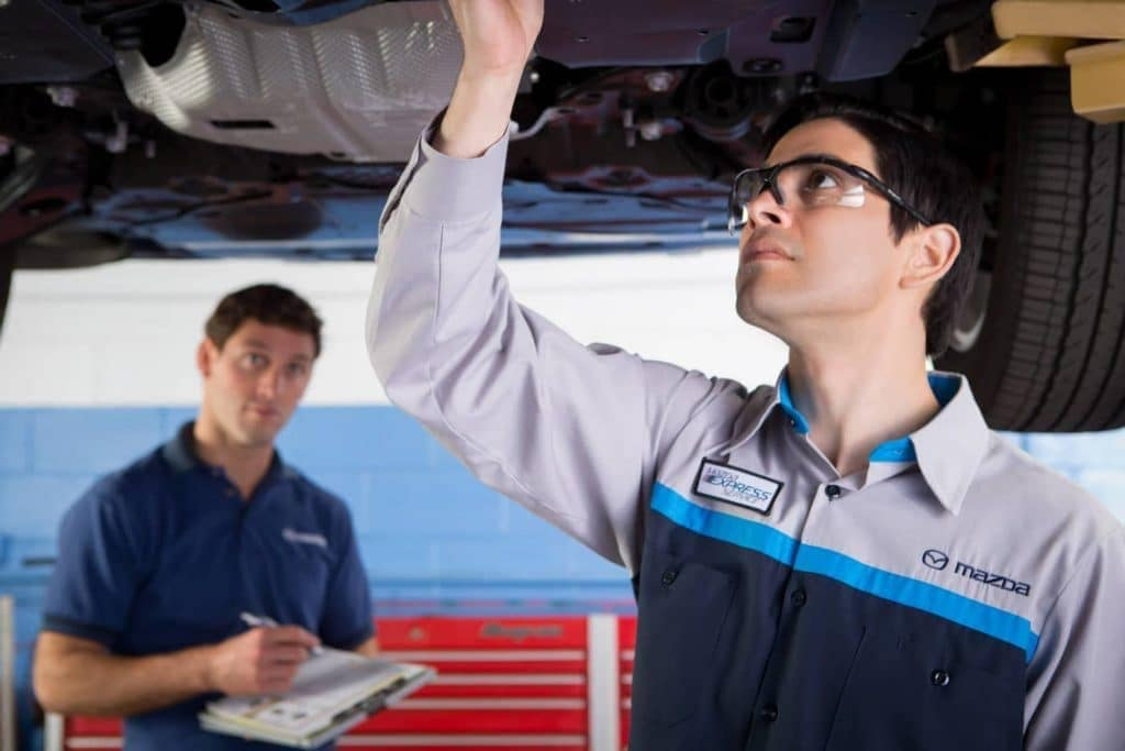 technician checking car undercarriage