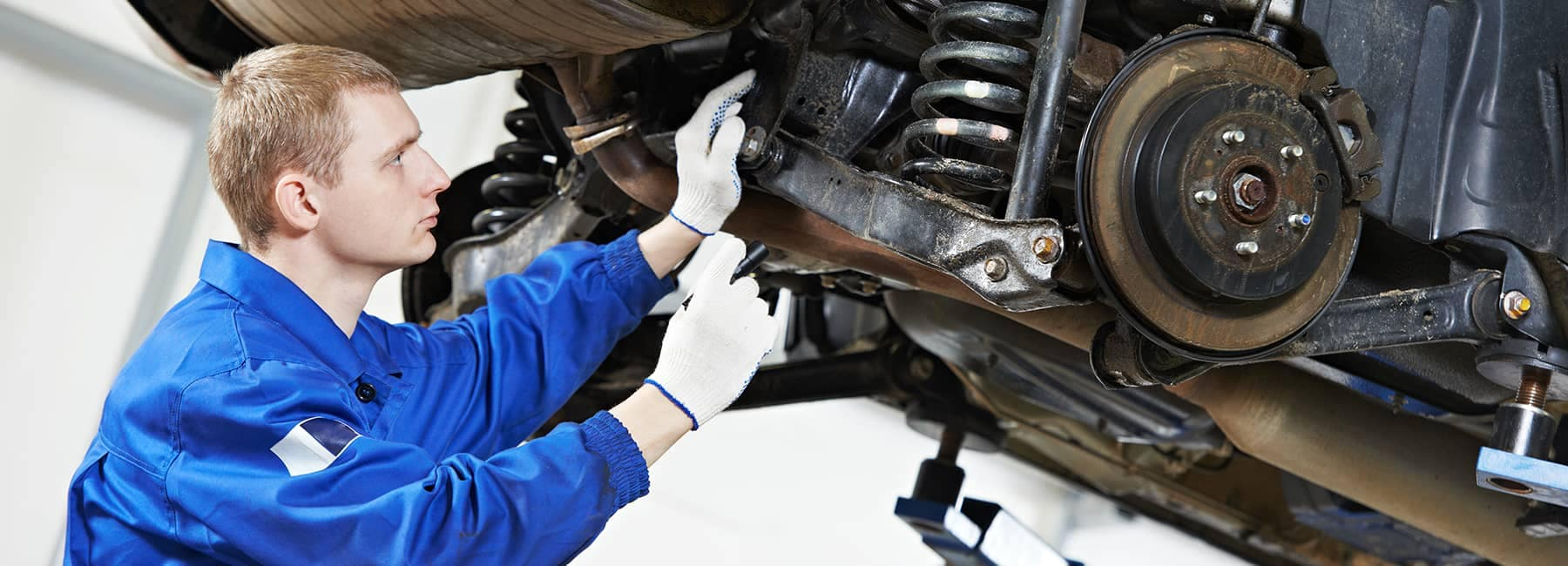 gloved technician examines underside of car
