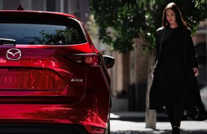 Red Mazda and woman on the left