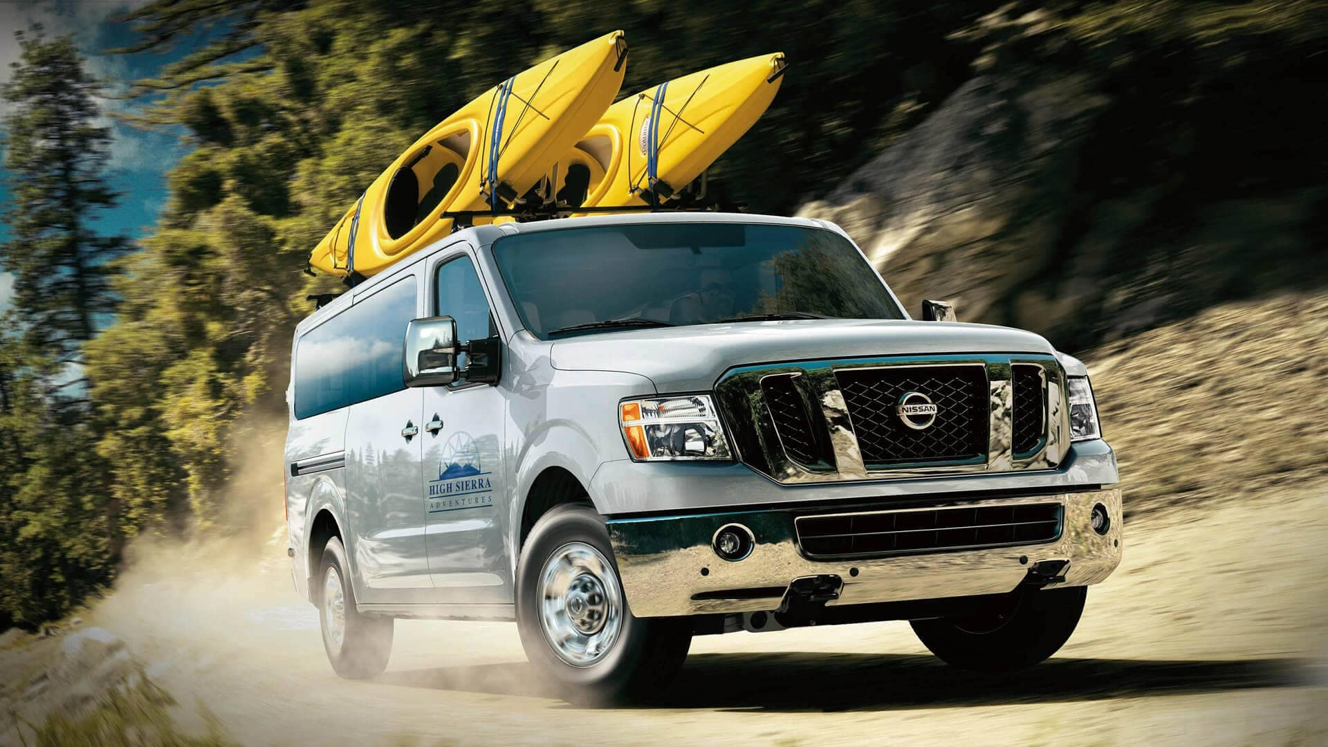 2020 Nissan NV Passenger with two kayaks on top driving on mountain road