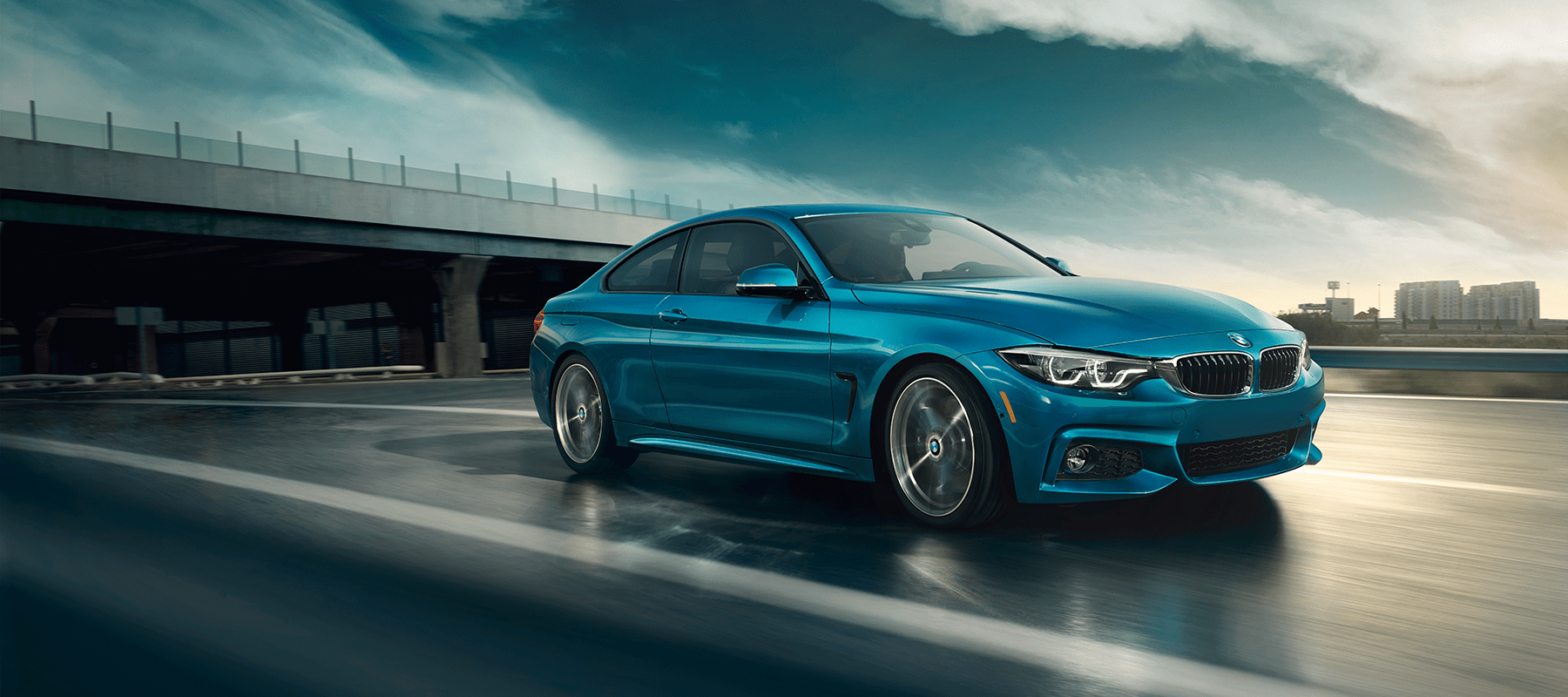 A Teel blue BMW 2019 4Series Coupe speeding down the road after a brief rain