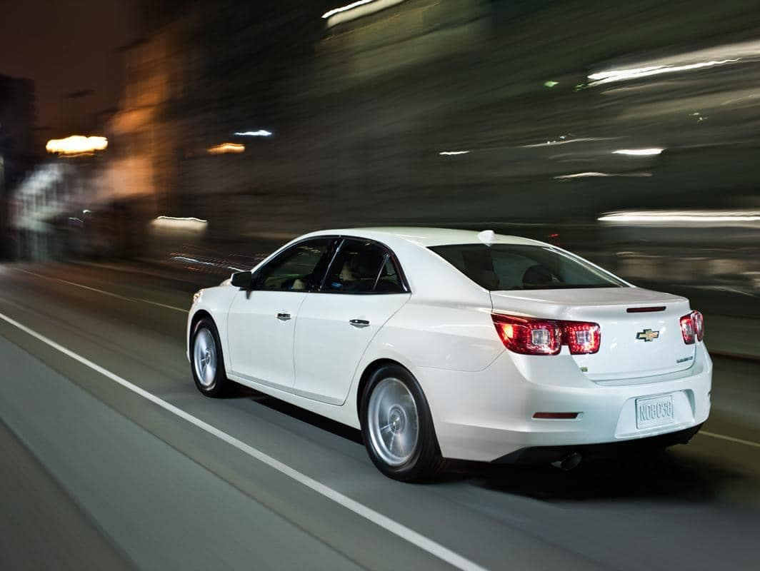 White Chevrolet Malibu cruises through a city streey