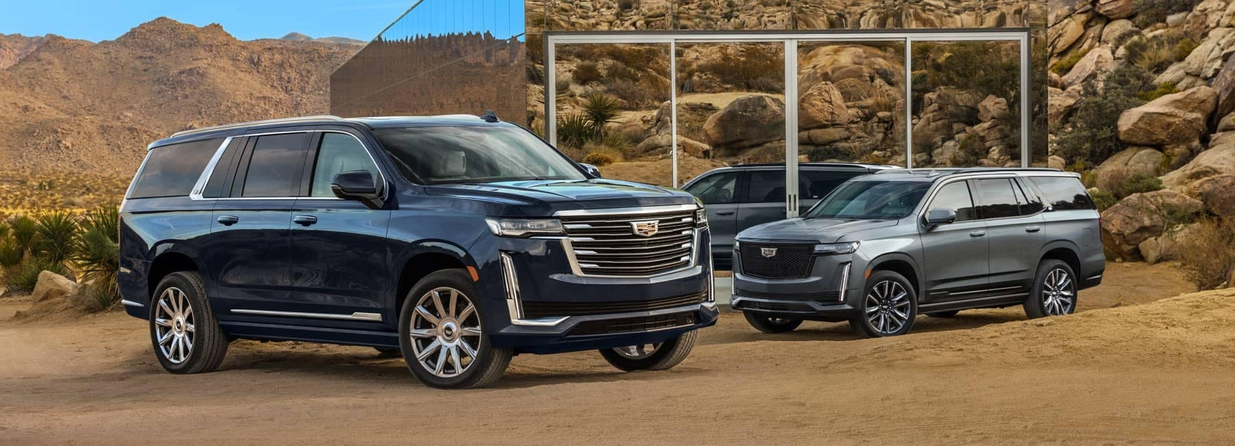 Two 2021 Cadillac Escalades parked in front of a glass house