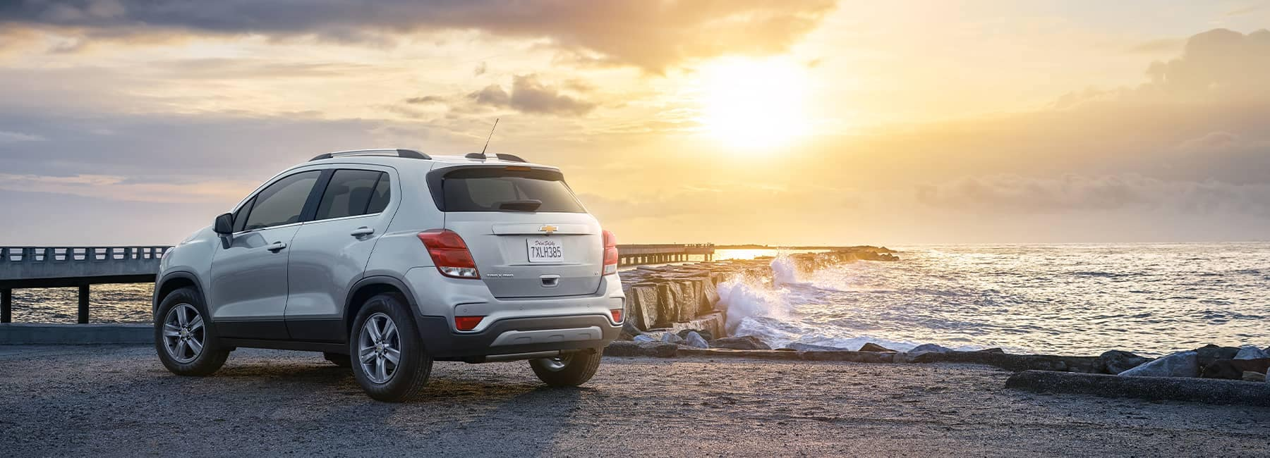 Rear view of a white 2021 Chevrolet Trax parked in front of an ocean pier