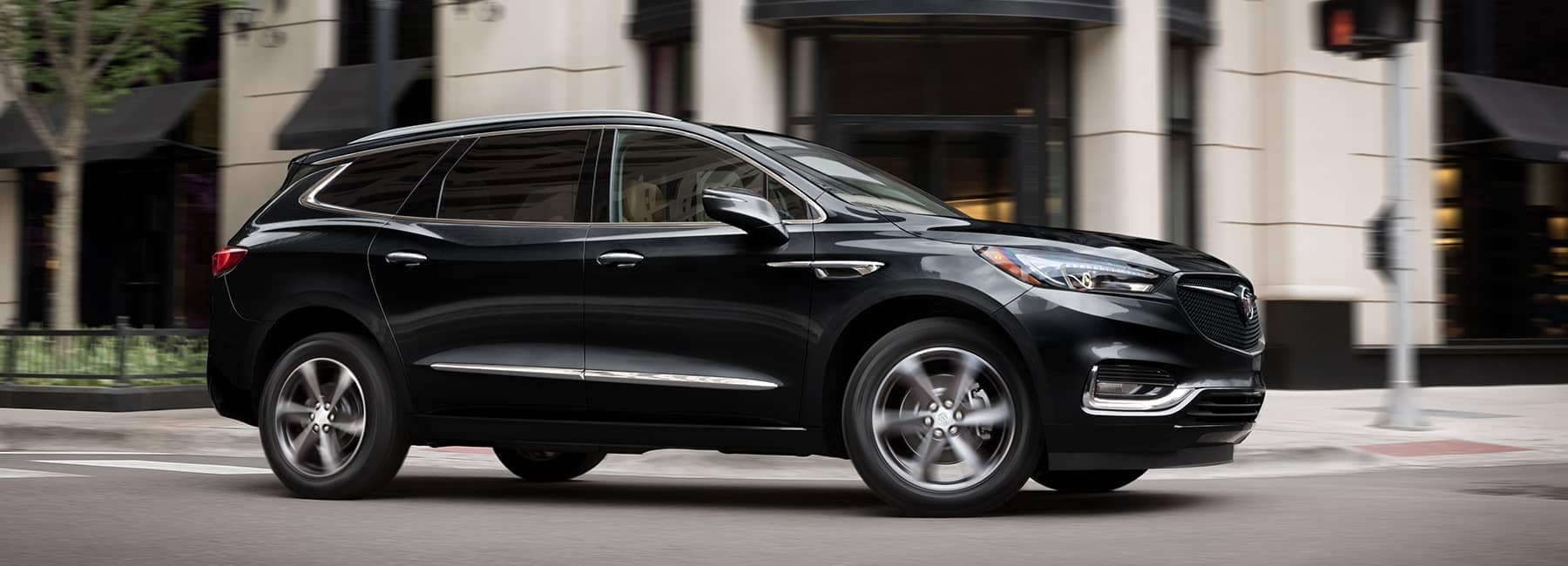 Black 2020 Buick Enclave drives through intersection