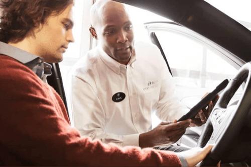 Service technician advises customer in his car