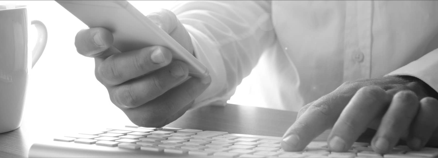 man typing on keyboard with coffee