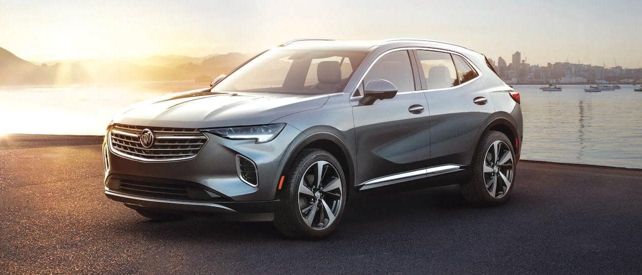 A gray 2021 Buick Envision is parked in front of a river and a city at sunset as part of the 2021 Buick Envision vs 2020 Buick Envision comparison.