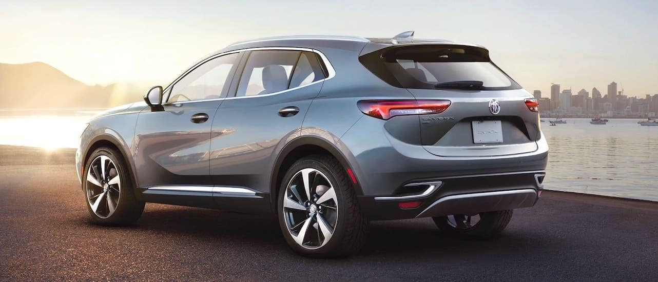 A 2021 Buick Envision is shown from the rear in front of a river and a city.