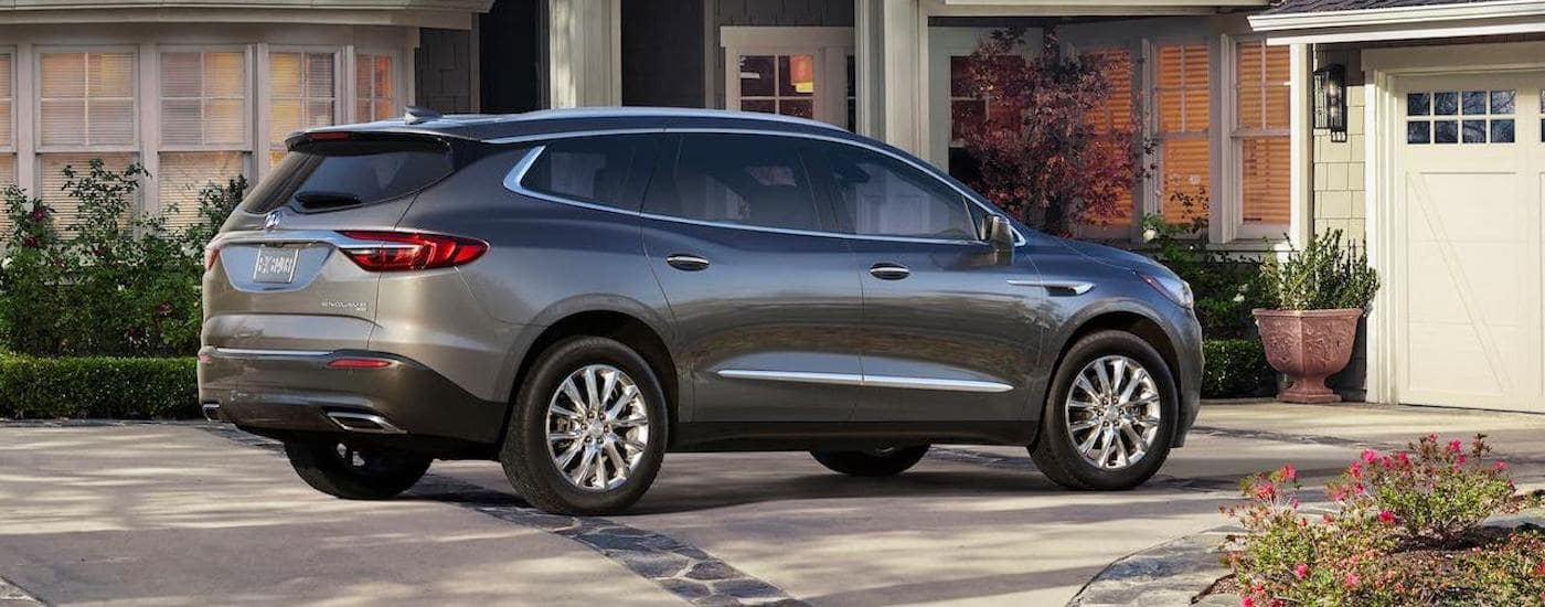 A gray 2019 Buick Enclave is parked in front of a Lexington, KY, home and shown from the side/rear.