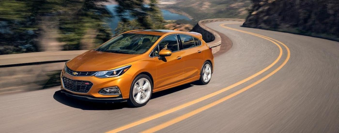 An orange 2018 Chevy Cruze Hatch RS is driving along a winding highway near Lexington, KY.