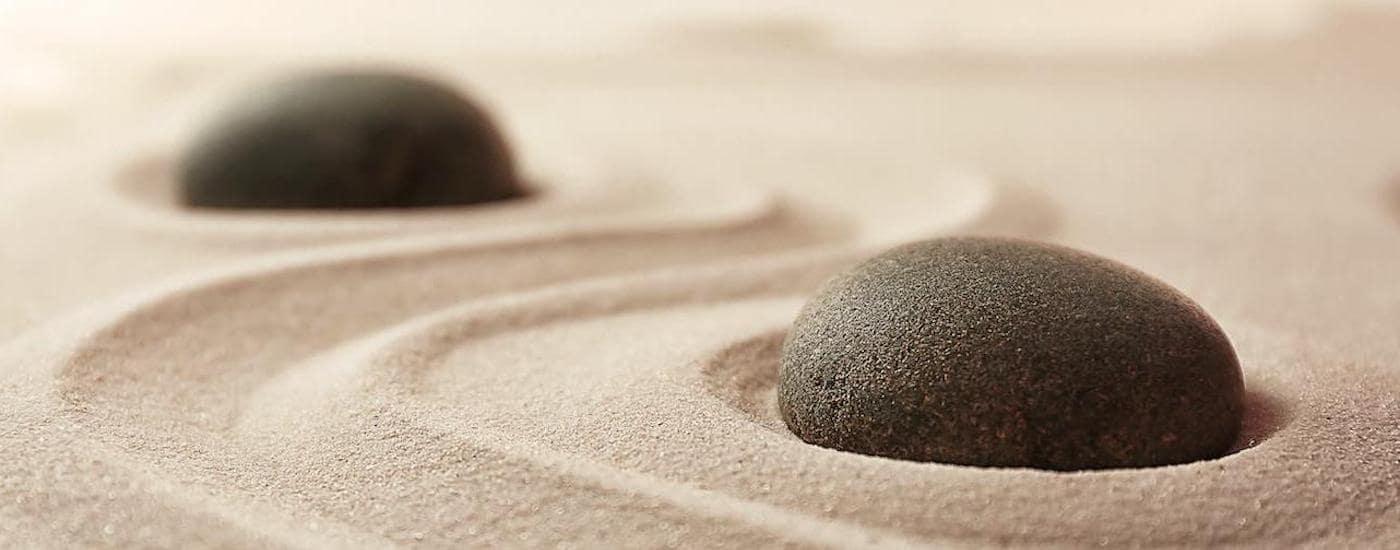 Two black stones are shown in a zen garden.