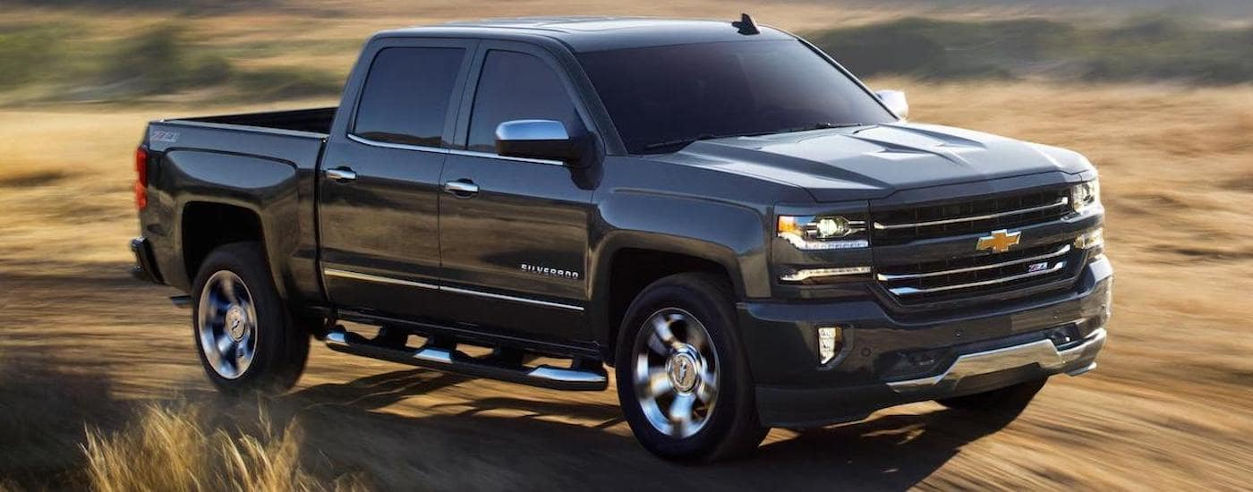 A black 2018 used Chevrolet Silverado 1500 Z71 is driving on a dirt road near Lexington, KY.