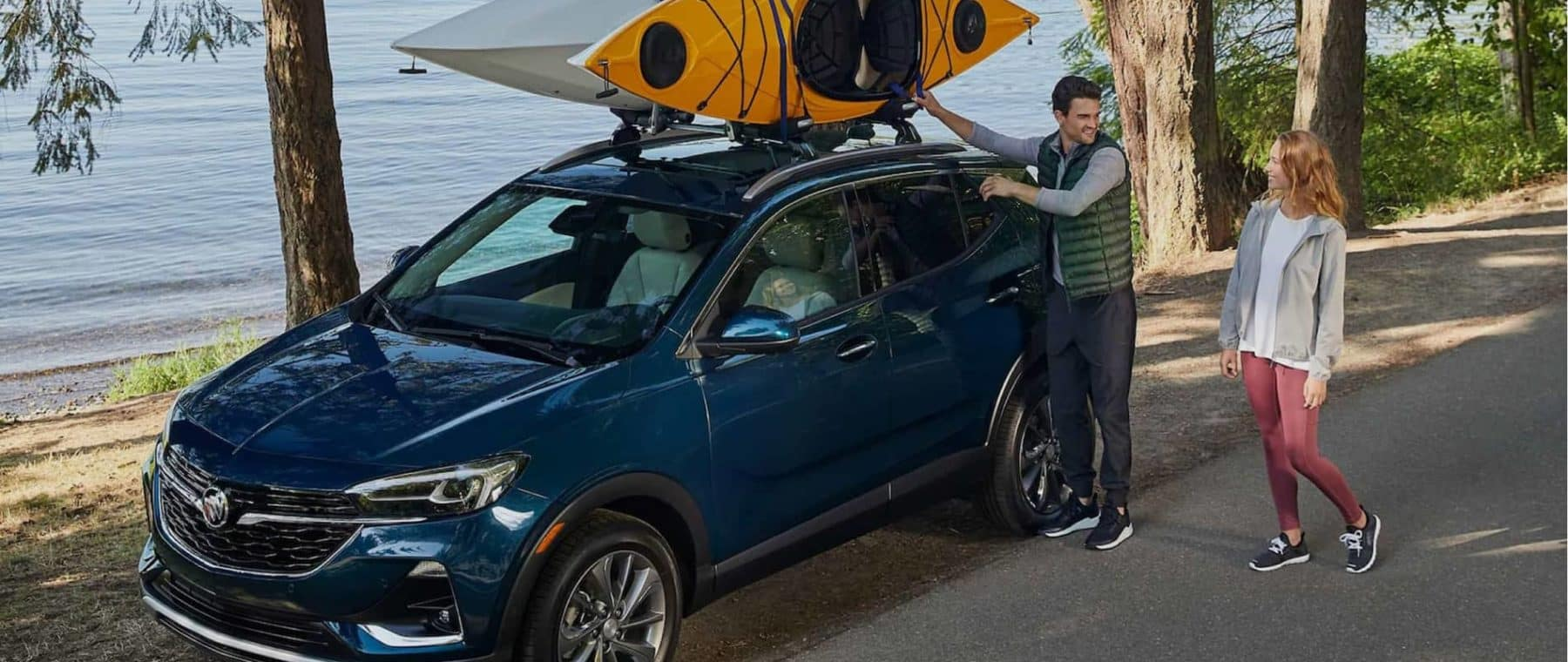 Couple attaching kayaks to the top of a Buick SUV