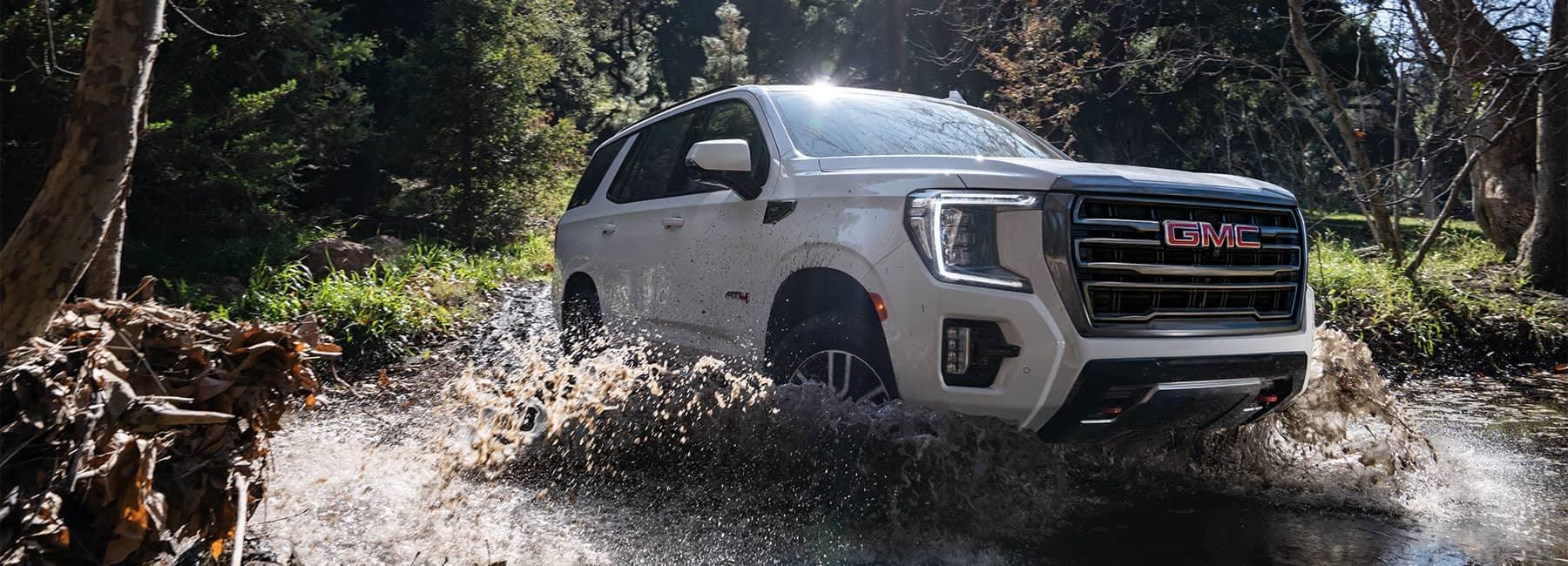 2021 Summit White GMC Yukon AT4 4WD driving through a forest stream