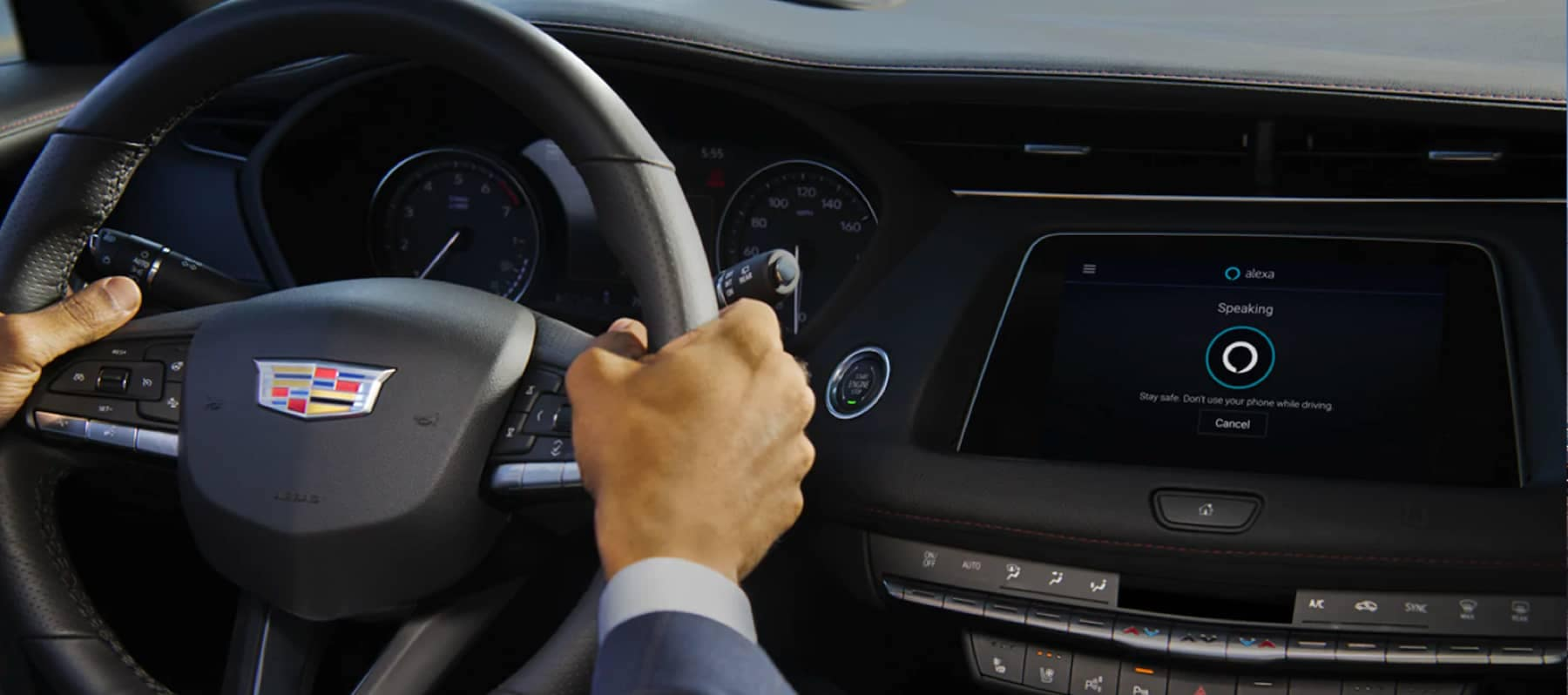 Hands on the steering wheel of a new Cadillac