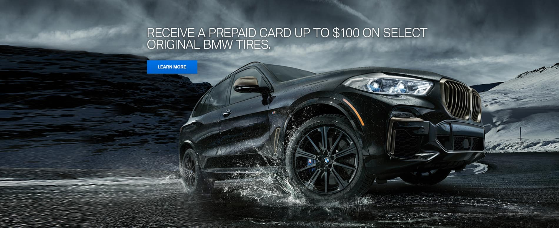 Three quarter view of a black BMW X5 with BMW Performance Star Spoke Style 748 M Jet Black Matte wheels rolling through a puddle creating a splash of water.