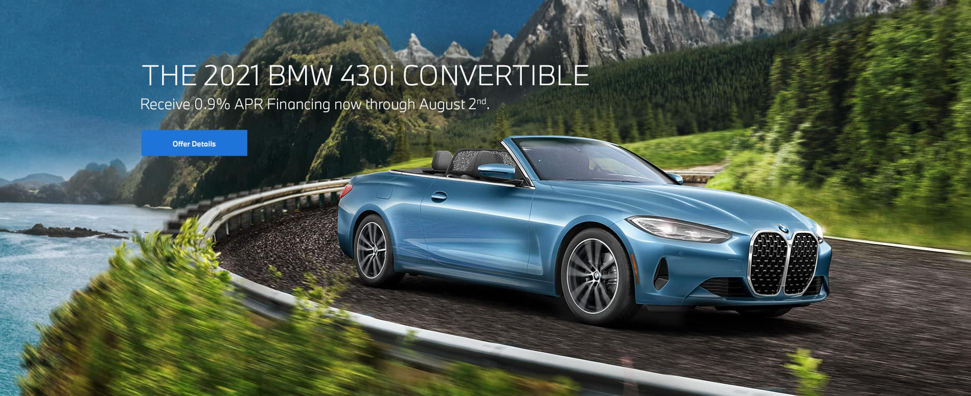 Blue 4 series convertible going around a bend on oceanside highway