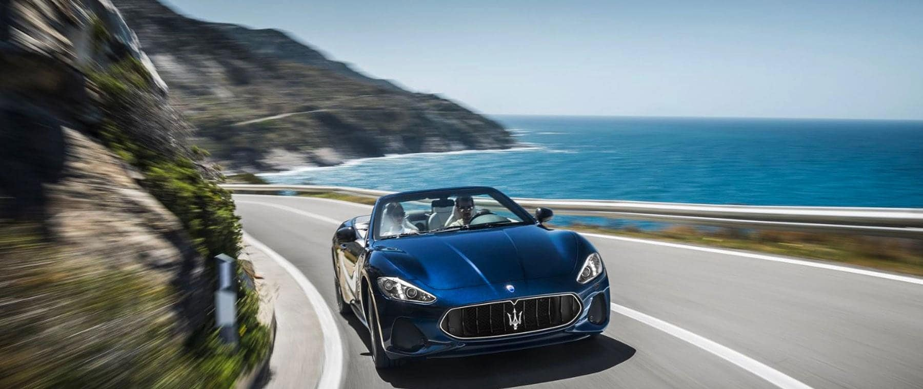 Blue Maserati convertible on ocean view road
