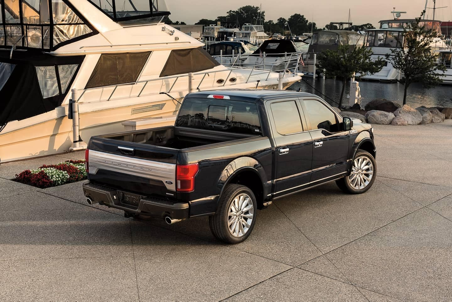 Ford F-150 parked next to boat in marina
