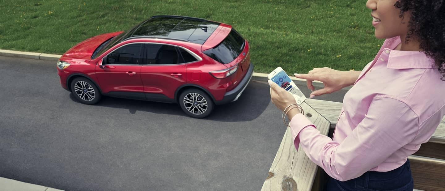 woman with smartphone looks down from balcony at Ford Escape