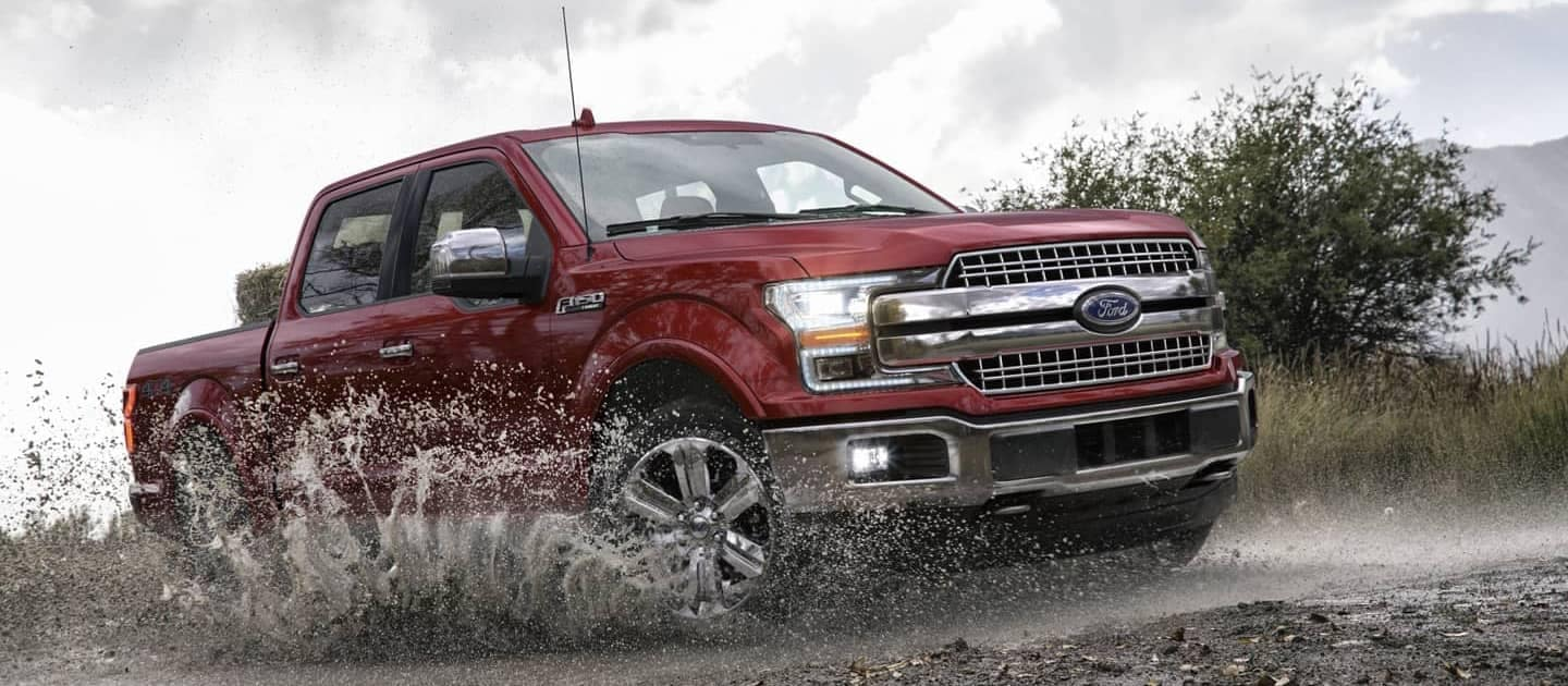 Red Ford F-150 driving through mud