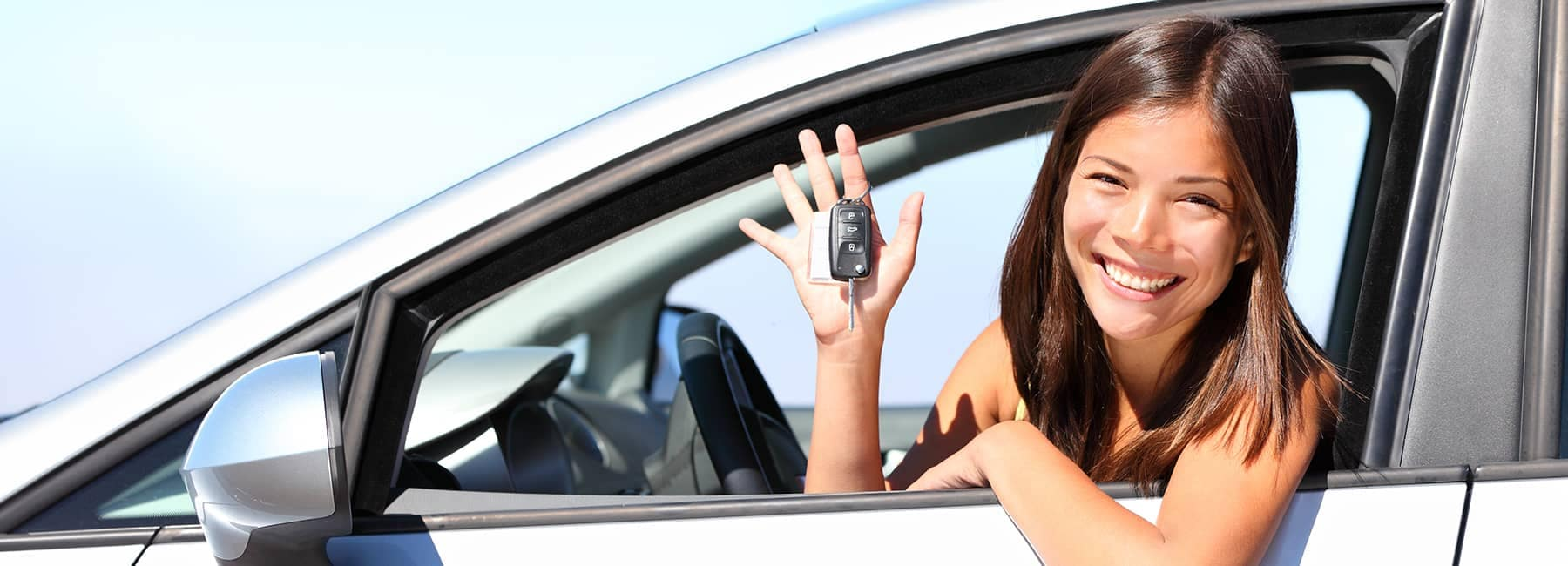 smiling car buyer holds keys in her hand in her new car