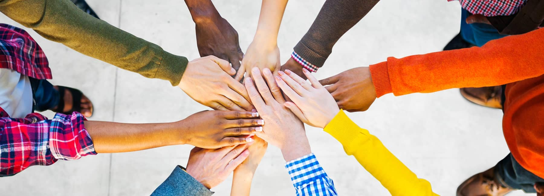 People Gathered in a Circle With Hands Together
