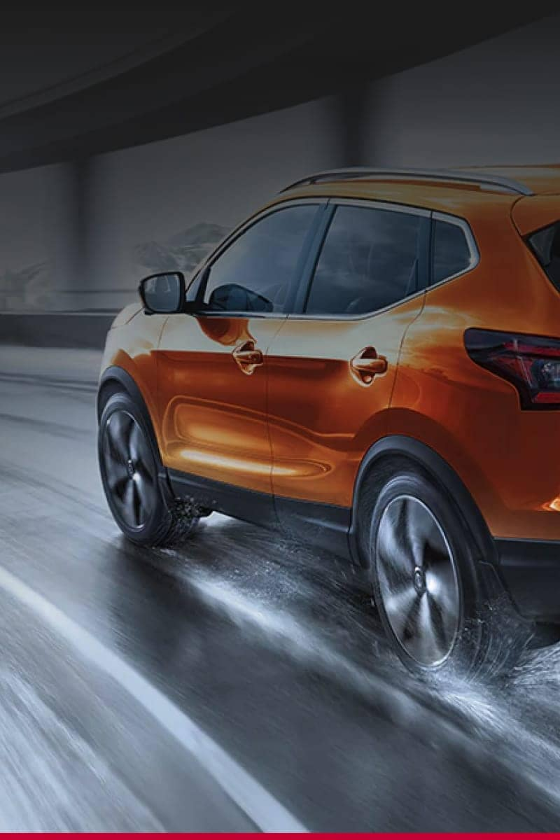 Sideview of an orange Nissan driving fast down a wet road.