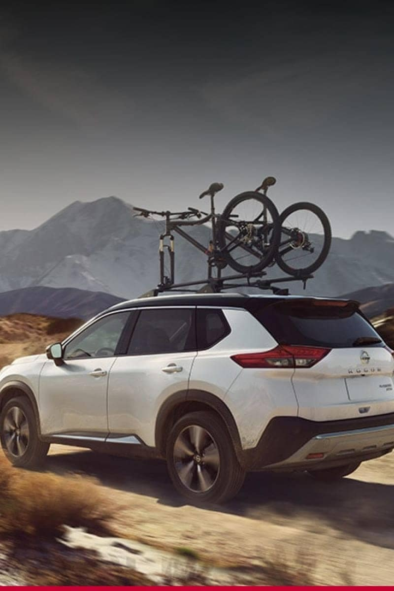 A white Nissan SUV with a bike on the roof rack driving through rough terrain.