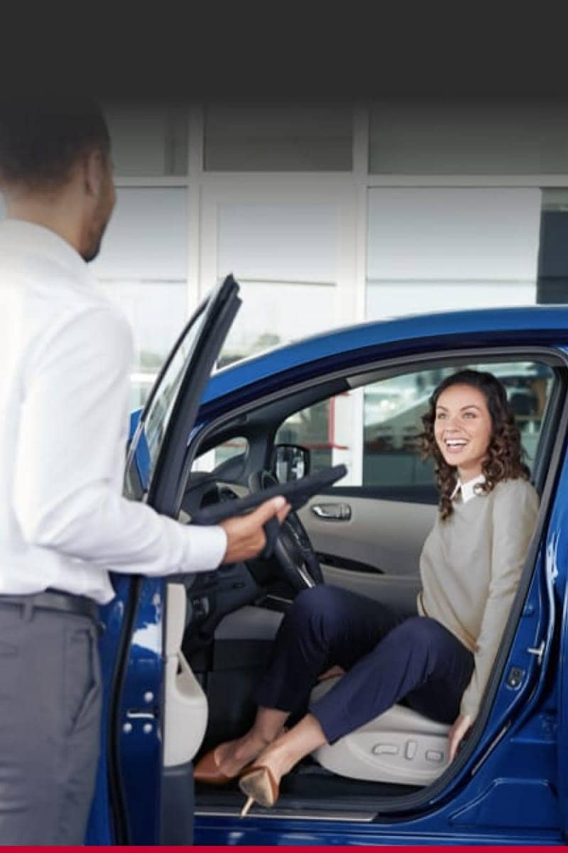 A woman sitting in the driver's seat of a blue vehicle talking to a salesman.