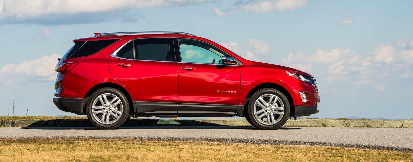 One of the popular Chevy SUVs in Suffolk, VA, a red 2020 Chevy Equinox is on a road against a cloudy blue sky and shown from the side.