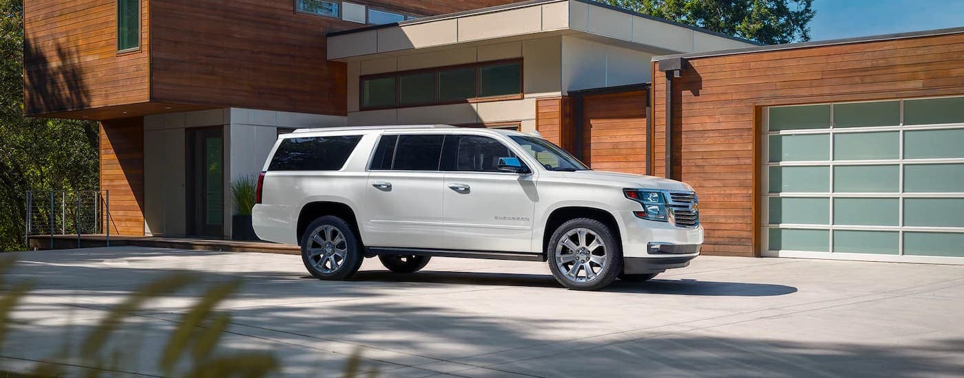 A white 2020 Chevy Suburban is parked in front of a modern home.