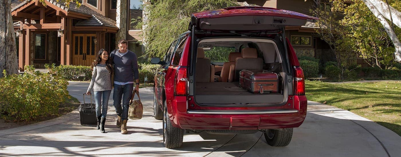 A couple is walking towards a red 2020 Chevy Tahoe that is parked in front of a modern home and has the liftgate open.