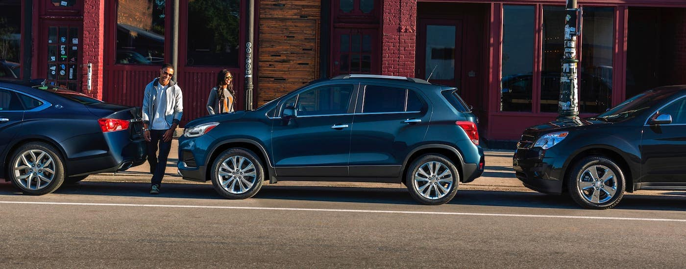 A couple is walking towards their blue 2020 Chevy Trax, shown from the side, which is parked in front of a Suffolk, VA, building.