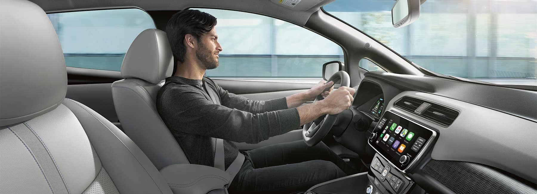 Young man driving a 2020 Nissan Leaf