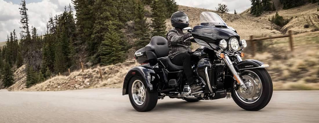 A motorcycle rider dressed in black riding a 2019 black Harley-Davidson Trike Tri-Glide Ultra on a mountain road.