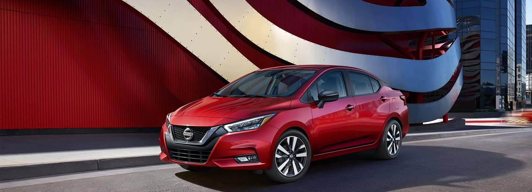 2020 Red Nissan Versa Exterior in Front of a Red Curved Wall
