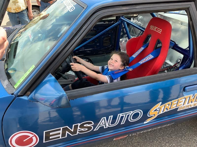 kid in a ens sports car