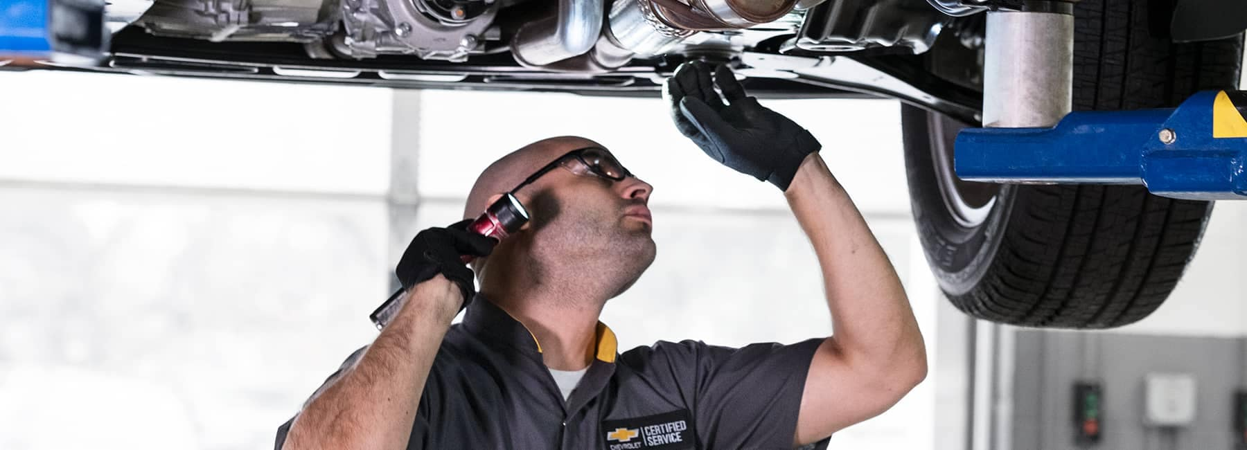 Chevrolet service technician looking at underside of a raised car