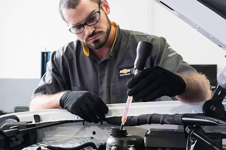 Chevrolet Service Technician looking at Cars Engine