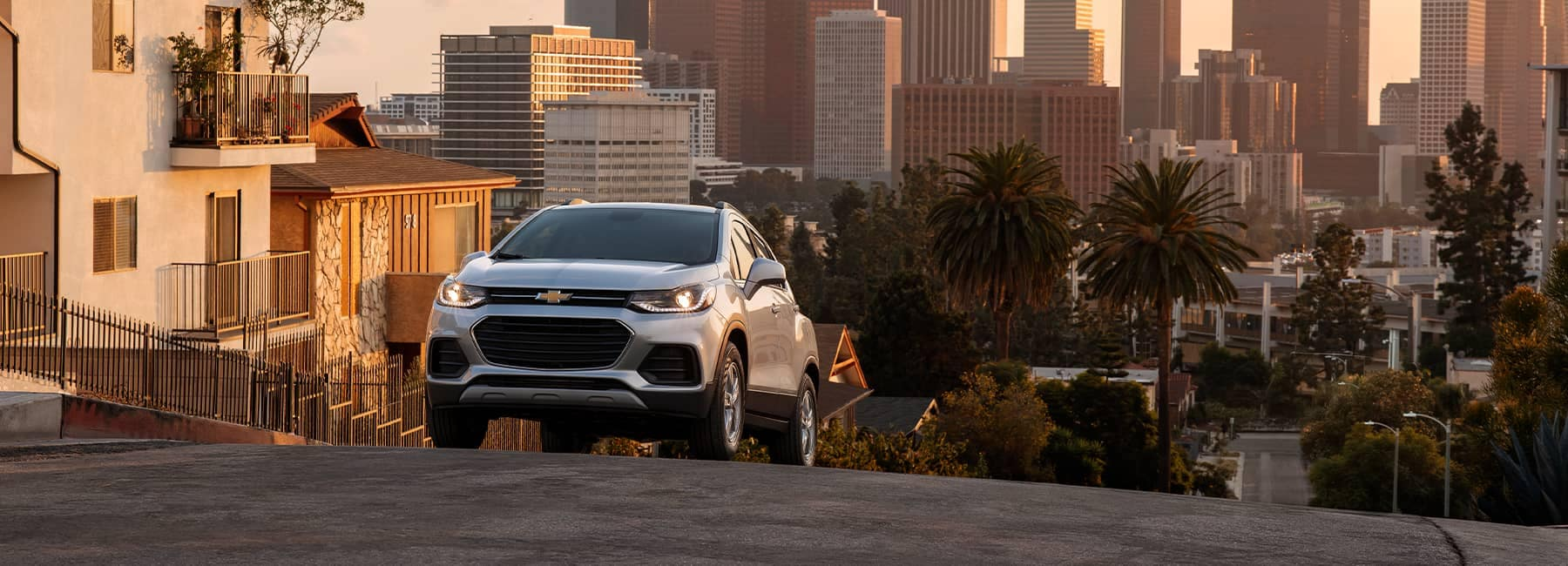 A silver 2021 Chevrolet Trax driving up a city hill at sunset