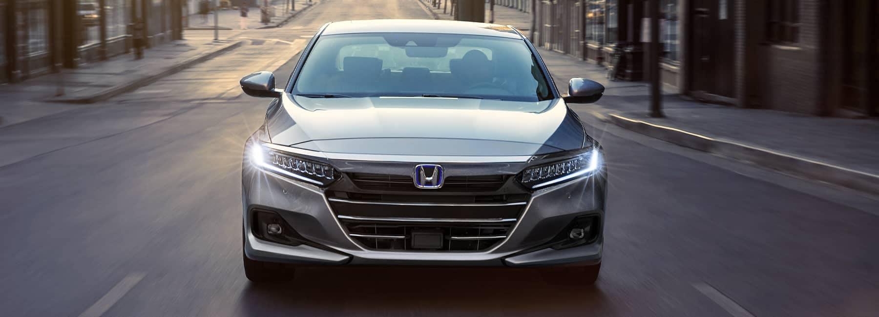 Front angle of a 2021 Silver Honda Accord driving up a city road