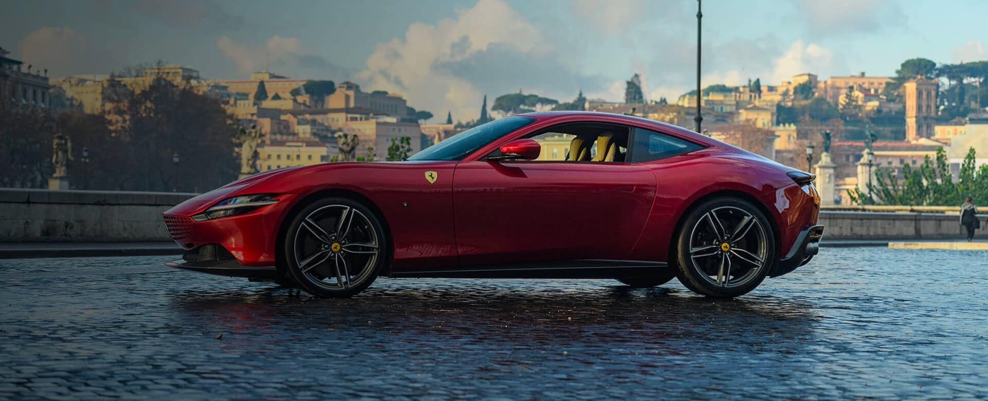 Red Ferrari on a damp cobblestone street in front of an Italian town
