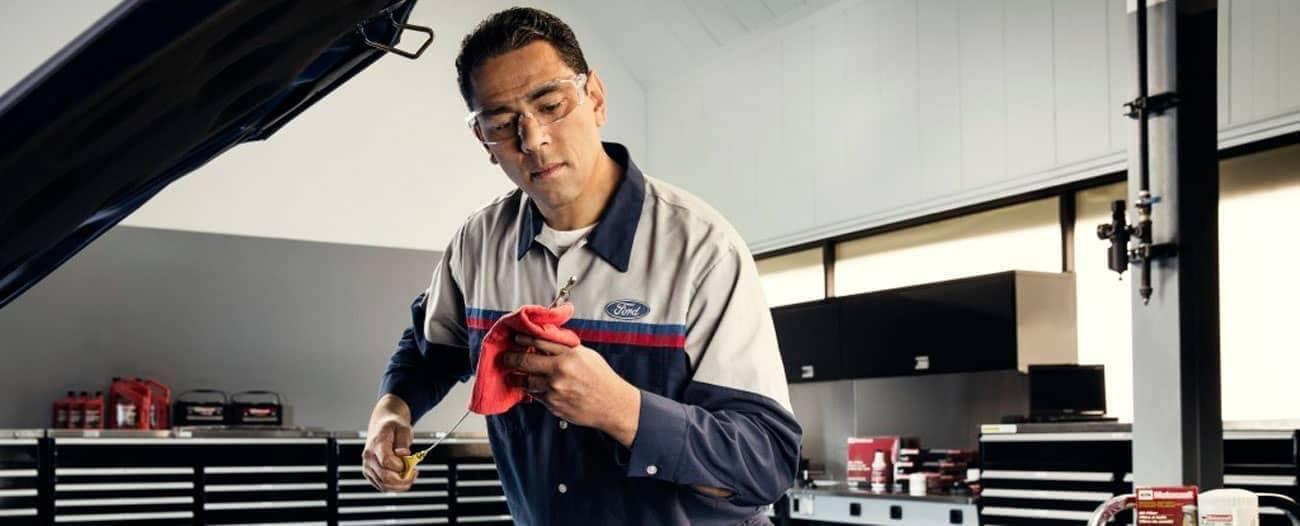 Ford-Service technician checks oil level