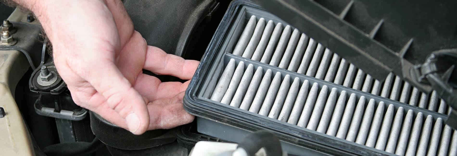 man lifting out car air filter