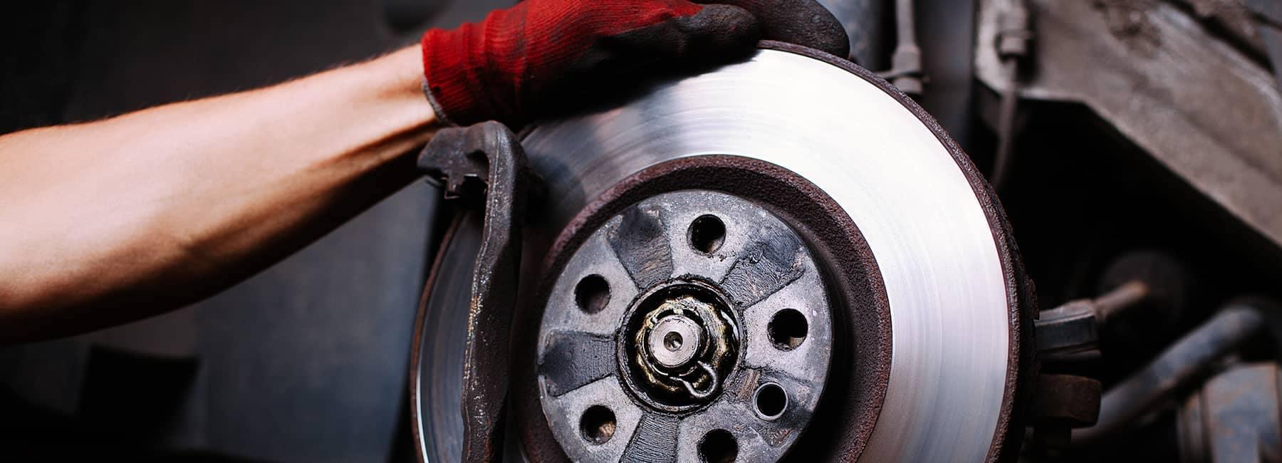 technician adjusts car brakes