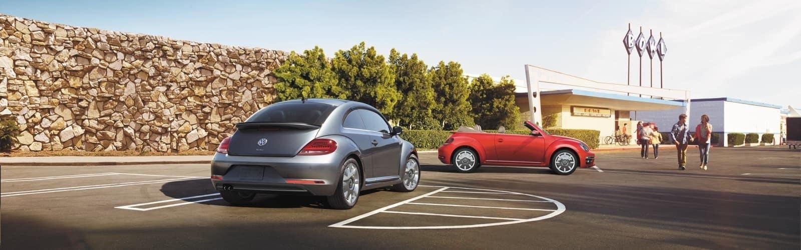 Volkswagen Beetles sitting in a parking lot