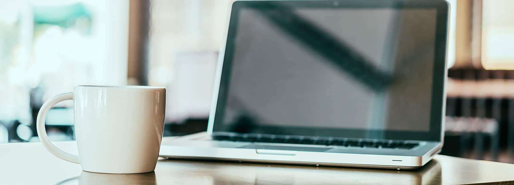 Computer and coffee mug