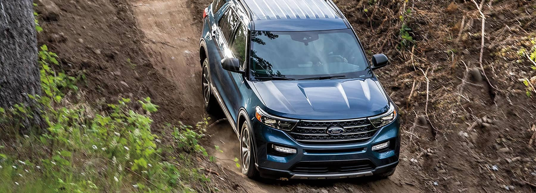 Blue 2021 Ford Explorer driving through a mud pass
